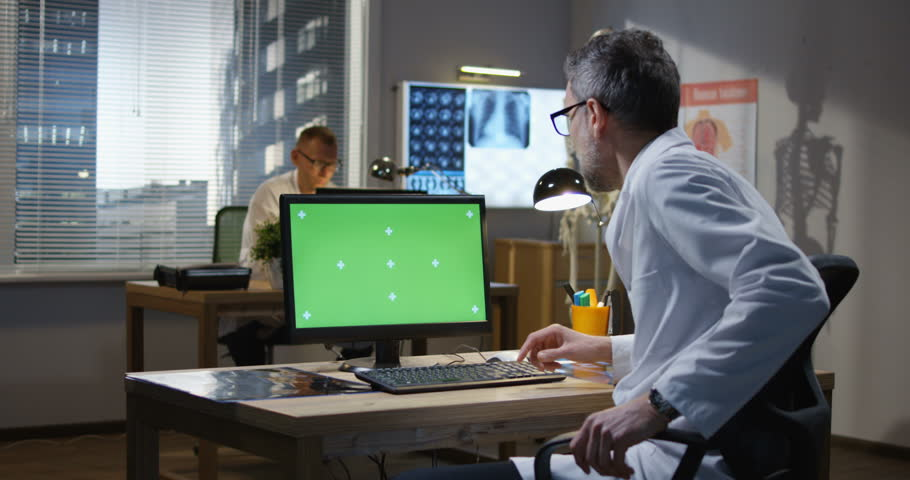 Medium shot of male doctor sitting at monitor and analyzing x ray | Shutterstock HD Video #1028760725