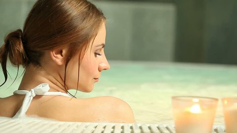 Beautiful young woman realxing at thermal bath in a beauty center. Girl with white bikini in hot tub. Relaxed woman in jacuzzi with white candles.
