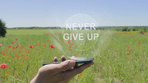 Hologram of Never give up on a smartphone. Person activates holographic image on the phone screen on the field with blooming poppies