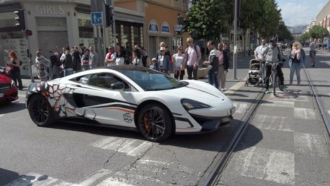Nice, France - May 1, 2019: Man Driving An Expensive McLaren 570S White Sports Car In The Avenue Jean Médecin Street In The City Center Of Nice On The French Riviera, Provence-Alpes-Cote d'Azur - 4K