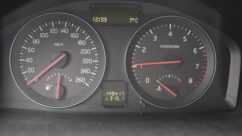Closeup of a dashboard from a car. Showing the car standing still but testing the engine by pushing the pedal.