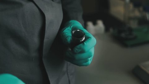 Scientist with green gloves spoons out a small amount of graphite from a test tube