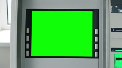 Close up view of ATM machine with green screen and blinking green signal. Cash machine or money dispenser machine with green screen. Technologies, money and cash, chroma key screen. Close up view