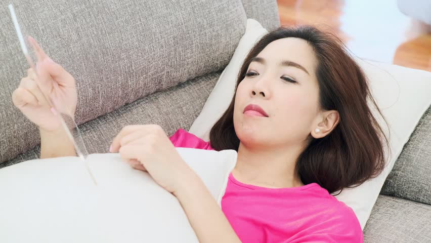 Young beautiful Asian woman browsing on transparent display on a couch in her living room. Future technology concept. For graphic overlay.