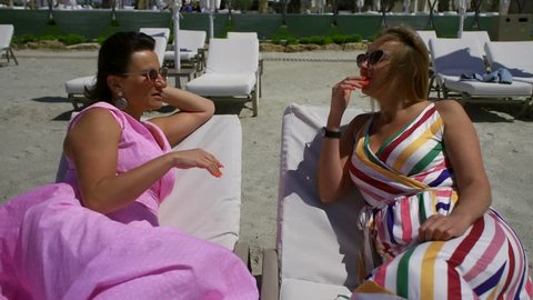 Two middle-aged female friends lie on the beach on the sun loungers and communicate. They're both tanned and wearing sunglasses. A dark-haired woman dressed in a pink dress
