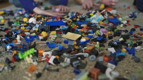 VINNITSA, UKRAINE - APRIL 2019: Unrecognizable hands throwing many lego blocks on the floor in the room. A lot of small colorful lego bricks in a mess lying on the carpet.