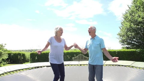 Slow motion sequence of senior couple bouncing on trampoline. Shot on Sony FS700 at frame rate of 100fps