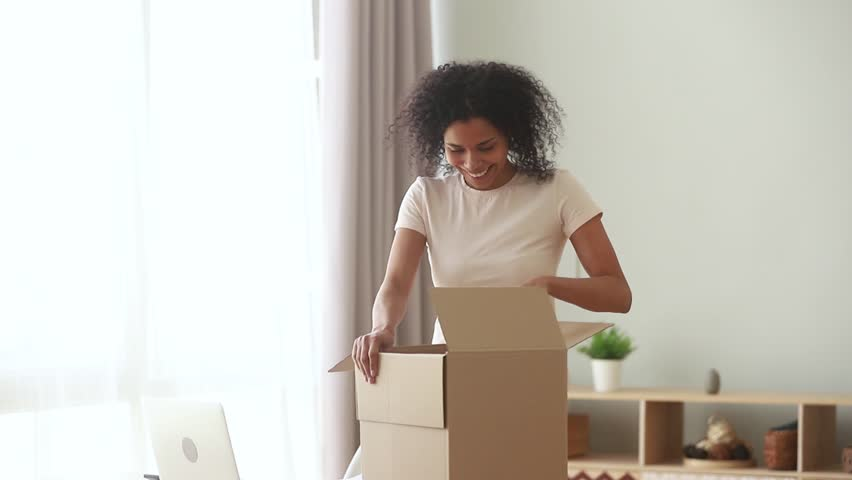 Happy excited african american woman customer open parcel at home, satisfied black girl consumer unpack cardboard box package looking inside receive postal shipping delivery, good purchase concept