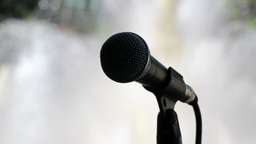 Black microphone on the stand in the Park on the background of the fountain. | Shutterstock HD Video #1028904245