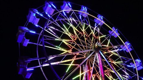 brightly lit ferris wheel ride spinning at night at a carnival, amusement park, theme park, fair, thrill park.