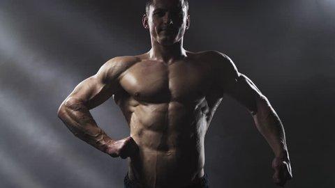 Handsome shirtless athletic man posing on a dark background. Athletic bodybuilder posing