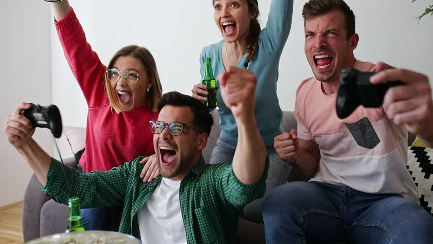 Group of friends sitting on sofa in living room and playing video games at home.	 | Shutterstock HD Video #1028976095
