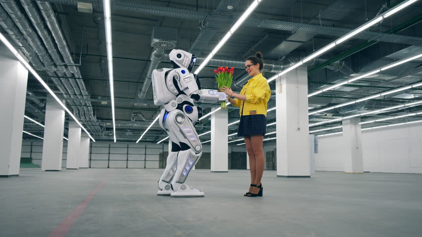 Lovely lady is accepting flowers from a human-like robot | Shutterstock HD Video #1028988485