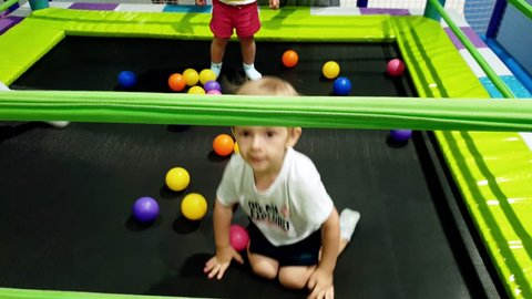 4k footage of cheerful smiling toddler boy jumping on trampoline on the playground at shopping mall