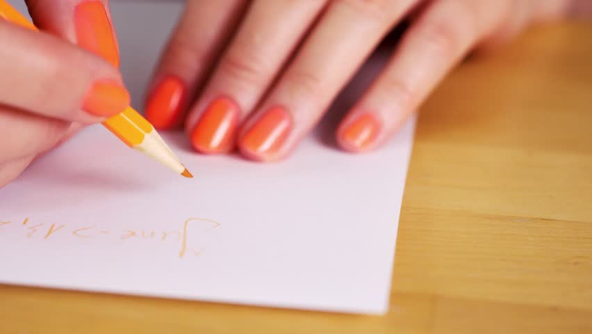 Woman is holding an orange pencil and makes notes on a white sheet on a wooden table | Shutterstock HD Video #1029044075