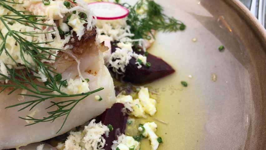 Closeup of sensational fish dish Back of cod with beetroot and clarified butter sprinkled with shrimps dill and horseradish | Shutterstock HD Video #1029046145