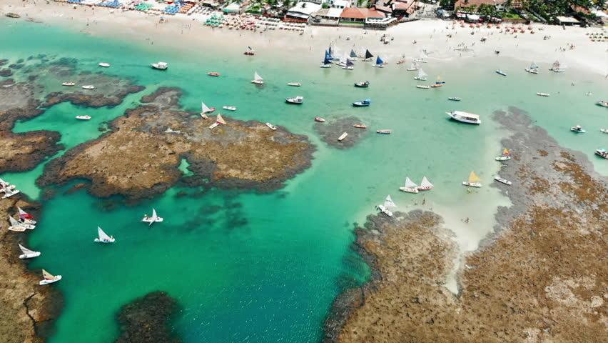 Aerial Forward: Amazing Tropical Beach with Colorful Boats and Beach Umbrellas in Porto de Galinhas, Brazil