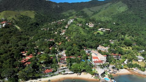 Aerial: Vast View of Ilhabela's Rich Green Jungle, Resorts and Vibrant Coastline in Ilhabela, Brazil