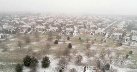 PITTSBURGH, PENNSYLVANIA, US. Snow covered suburban estate street and houses during heavy winter snowfall. Aerial 4K view of buildings and trees after snow storm.