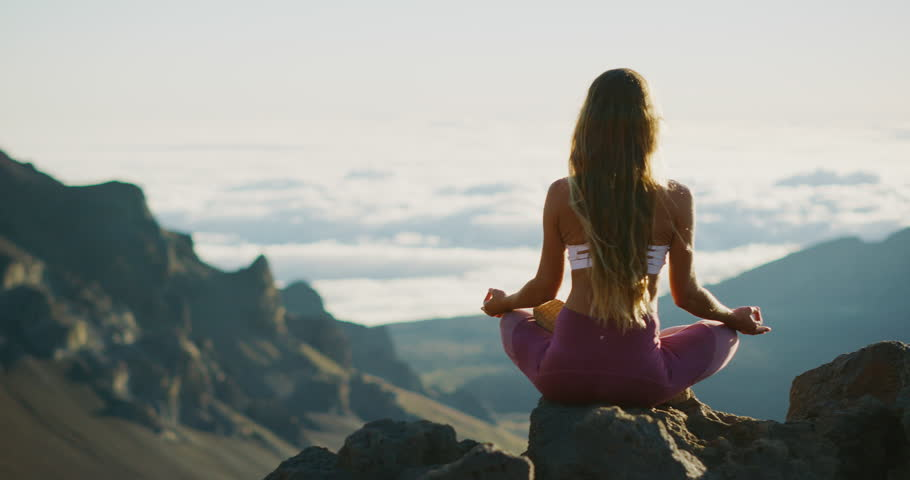 Young athletic woman meditating on the top of a mountain, zen yoga meditation practice in nature