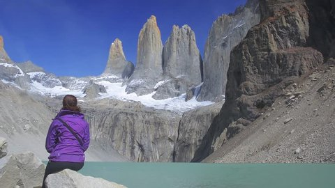 Young woman is admiring Paine Towers (The Torres del Paine) sitting by the lake in Torres Del Paine National Park, Patagonia, Chile. Travel and adventure concept.
