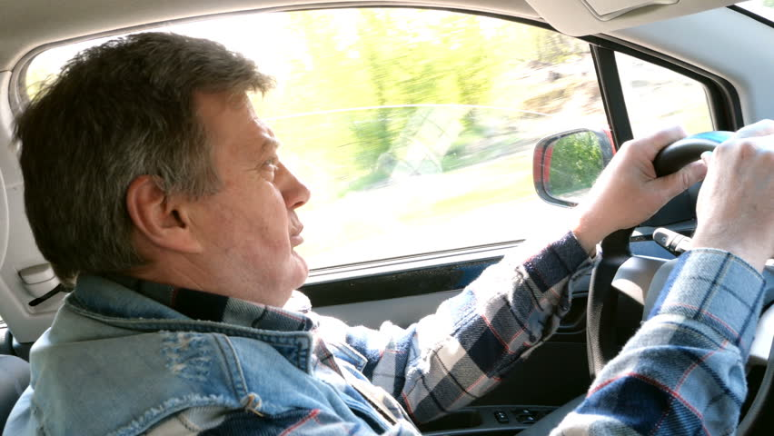 Adult man drives his car, turns the steering wheel and looks ahead with surprise. View from the passenger seat.