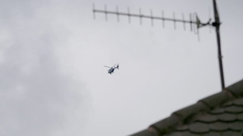 Cinematic view surveilling Gendarmerie French police helicopter during French yellow Vests Gilets Jaunes protest flying above roofs and houses
