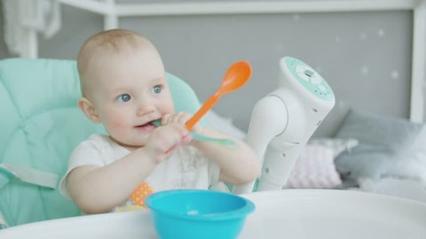 Close-up of teether toddler girl sitting on feeding chair in front of empty plate and gnawing plastic spoon. Cute infant teething and biting spoon before eating on chair for babies in children's room.