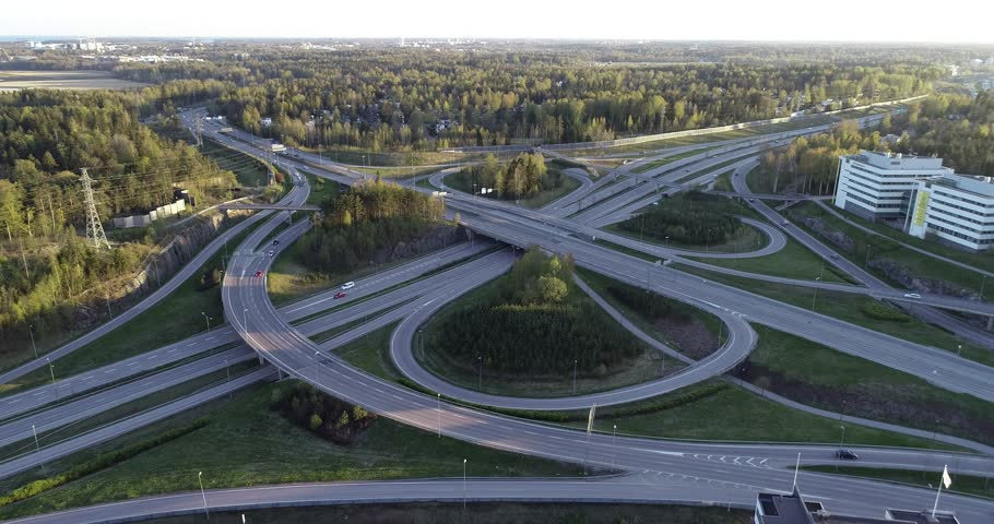 A modern flyover road junction in a large metropolis. Aerial video footage a drone from a altitude. Sunny summer evening, sunset. Top down view.   | Shutterstock HD Video #1029155375