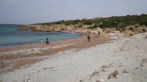 Sand dune with sparse vegetation of a European desert with emerald sea of Ostriconi beach. Shrubs of Mediterranean scrub on sandy dunes. Desert des Agriates, Balagne region, Corsica, France