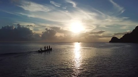 Aerial, drone shot, a silhouette of people standing on a boat, driving on the coast of St Lucia, on the calm Carribbean sea, on a sunny, summer day, in Lesser Antilles