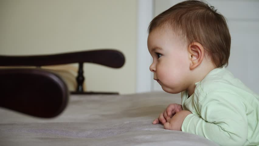 Toddler baby standing near sofa and watching cartoons calm and concentrated at home, calm time | Shutterstock HD Video #1029191915