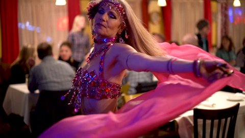 Slow motion closeup of belly dancer spinning with pink veil in a restaurant.