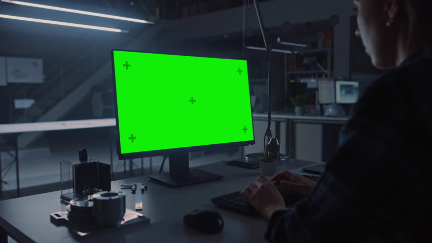 Over the Shoulder Shot of Engineer Working with Green Mock-up Screen Desktop Computer. In the Background Engineering Facility at Night Blueprints and Drawings with Showing Industrial Design | Shutterstock HD Video #1029209465