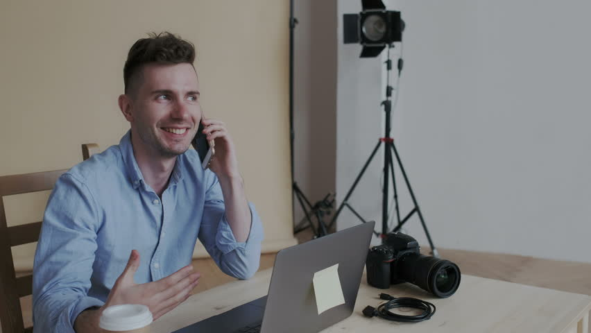 Handsome sociable man speaking on the phone with a lot of positive emotions. He sitting in creative workspace with laptop and photo camera. Studio photography tools on the background.   Shutterstock HD Video #1029225245