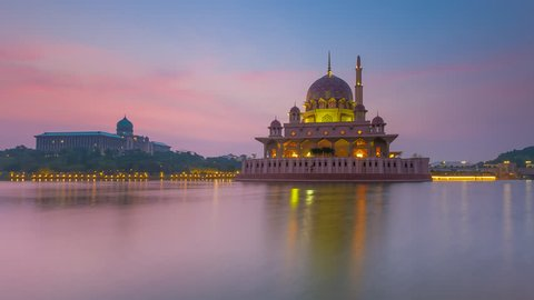 Hazy Cloudy sunrise Time Lapse at Putra Mosque by a lake in Putrajaya, Malaysia at dawn.