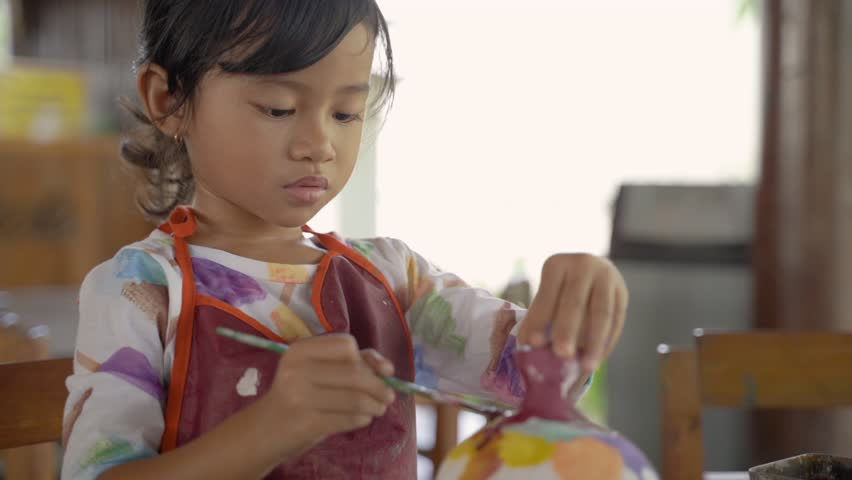 Asian child painting ceramic pot with paint brush in pottery workshop | Shutterstock HD Video #1029243365