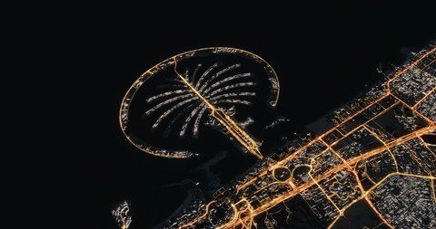 Aerial cinematic night view of Dubai artificial Palm Island at Jumeirah Beach. Camera flying sideways and panning. Street and traffic lights shining. 3d rendering animation. United Arab Emirates