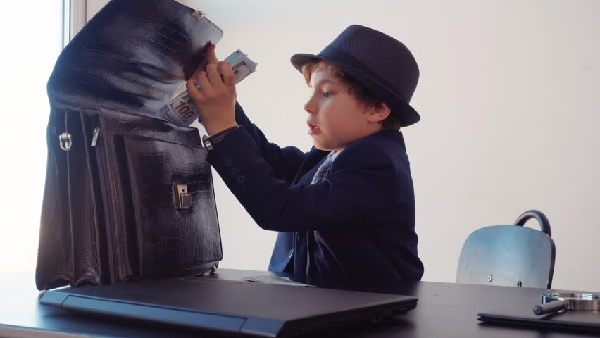 Little boy business boss at business table hiding money stack in briefcase in office. Young business boss in black suite and hat putting money cash in briefcase. Business children concept   Shutterstock HD Video #1029247955