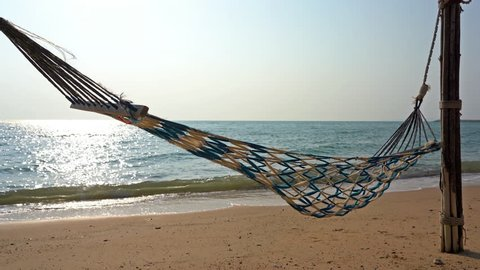 Woven blue and yellow hammock swinging with wind on sand near beach shore with sun reflecting aqua water sea at daytime on blue sunny sky
