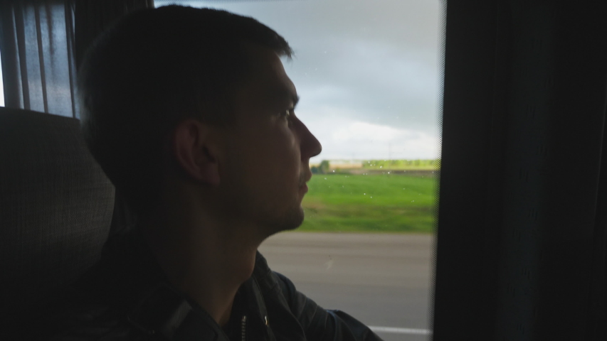 Man in bus looks out a window of the bus during a long trip in summer