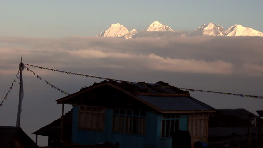 Epic view of hut with prayer flags sitting atop mountain above clouds with snow capped mountain peaks in the background in Nepal