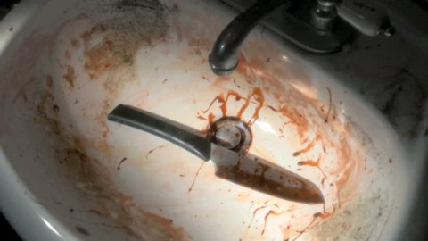 Bloody knife is dropped into dirty old sink, horror or murder concept