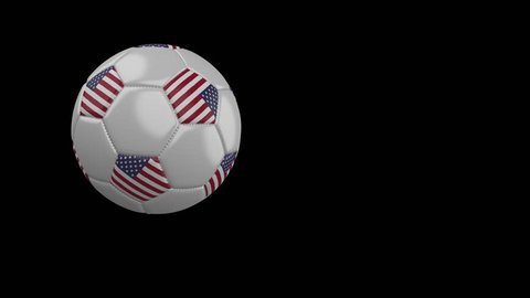 Soccer ball with the flag of United States of America flies past the camera, slow motion, 4k footage with alpha channel