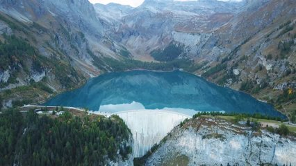 Water dam and reservoir lake aerial drone footage in Swiss Alps mountains generating hydro electricity power renewable energy and sustainable development