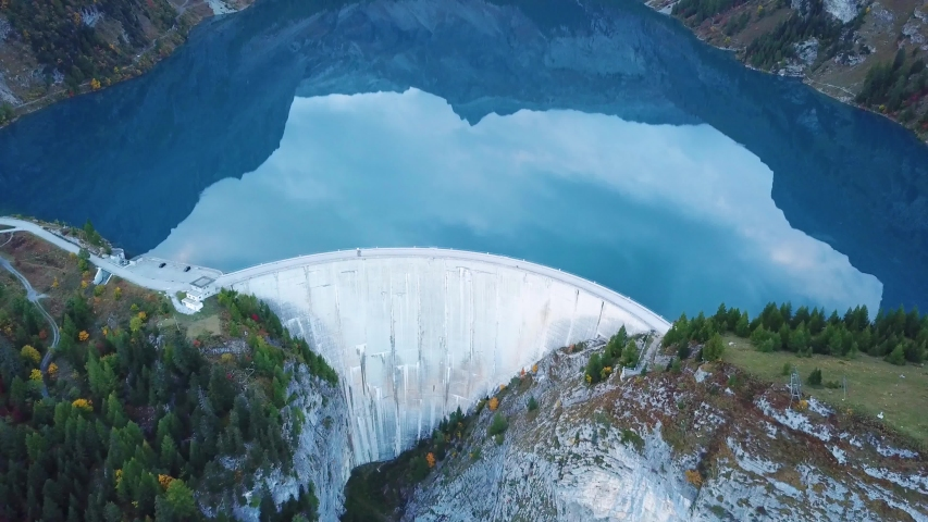 Water dam and reservoir lake aerial drone footage in Swiss Alps mountains generating hydro electricity power renewable energy and sustainable development. 4K 60fps video