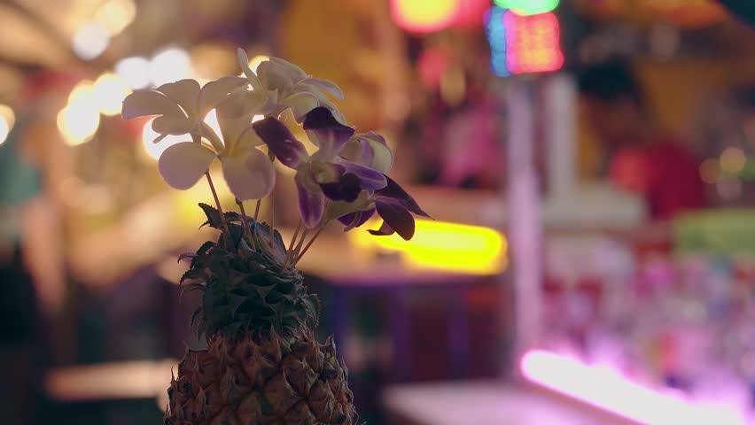 fresh pineapple with blooming orchids on neon blurred background of street market and working people close view