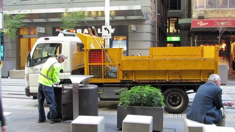 City of Sydney Workman collects garbage from bin and throws rubbish in the back of a small truck in the Pitt Street Mall, Sydney, New South Wales, Australia on 12 May 2019.