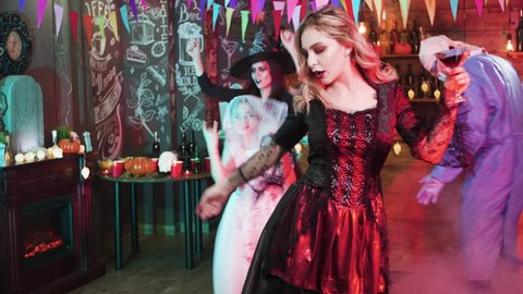 Sexy witch holding a glass of blood in her hands and dances slowly at a halloween party. People gathered at a halloween party and are having fun.