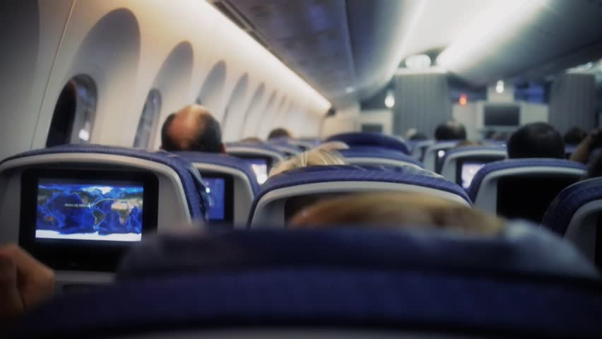 Passengers in comfortable seats of aircraft with the maps on screens in chairs